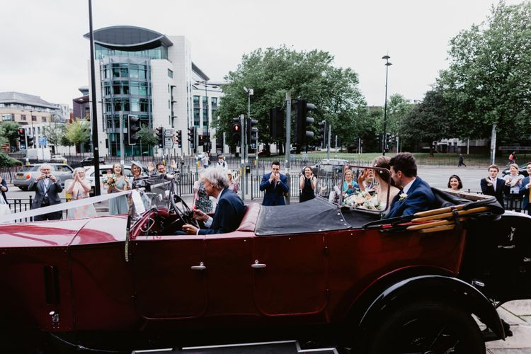 Bride and groom driving off in vintage wedding car