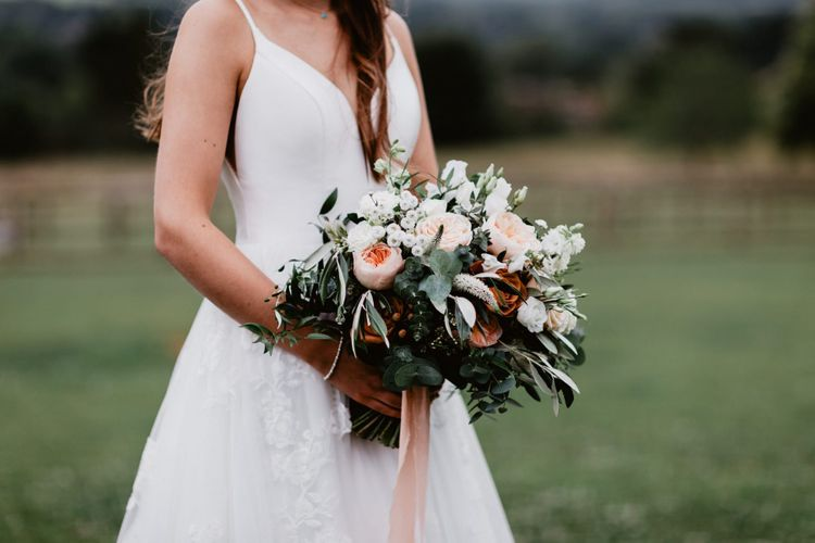 Bride holding a romantic peach and white flower bouquet with foliage and ribbon