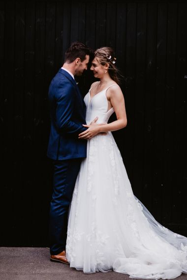Bride in Essense of Australia wedding dress and groom in navy blue suit embracing