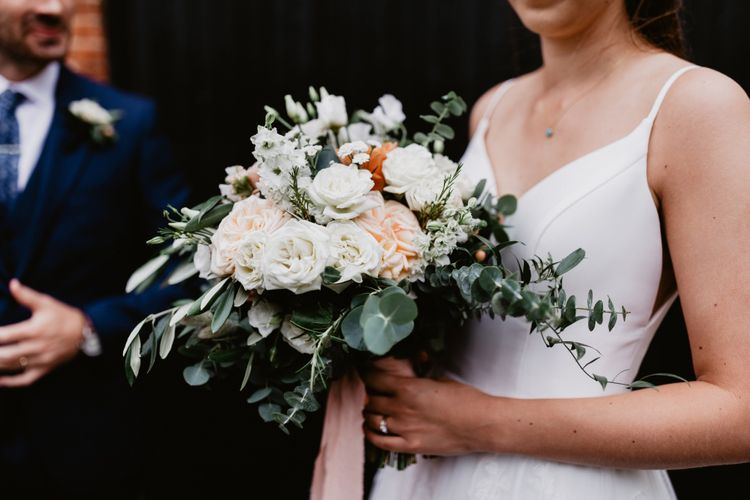 peach and white rose wedding bouquet tied with foliage and ribbon