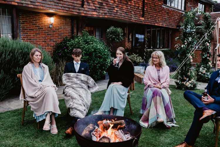 Wedding guests wrapped in blankets sat by the firepit