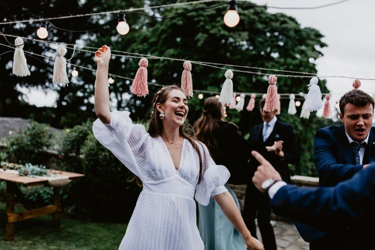 socially distanced wedding reception with festoon lights and tassels