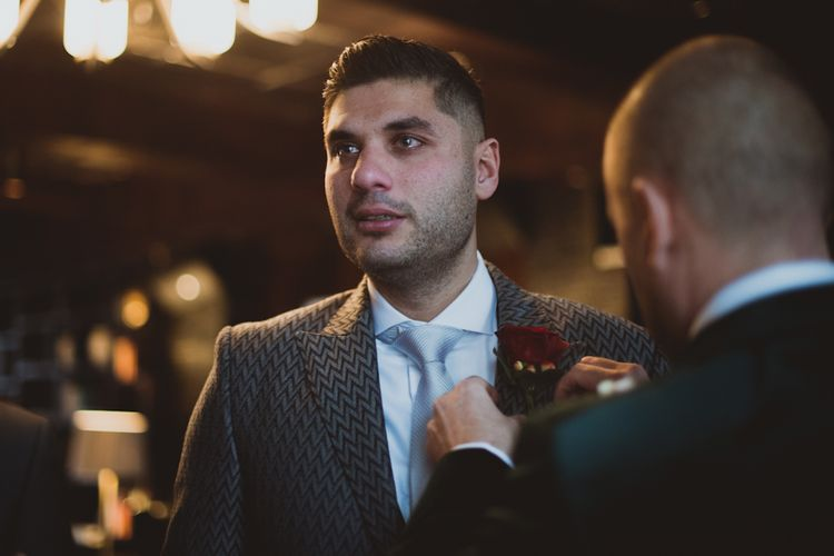 Groom Gets Buttonhole Placed On Wedding Suit