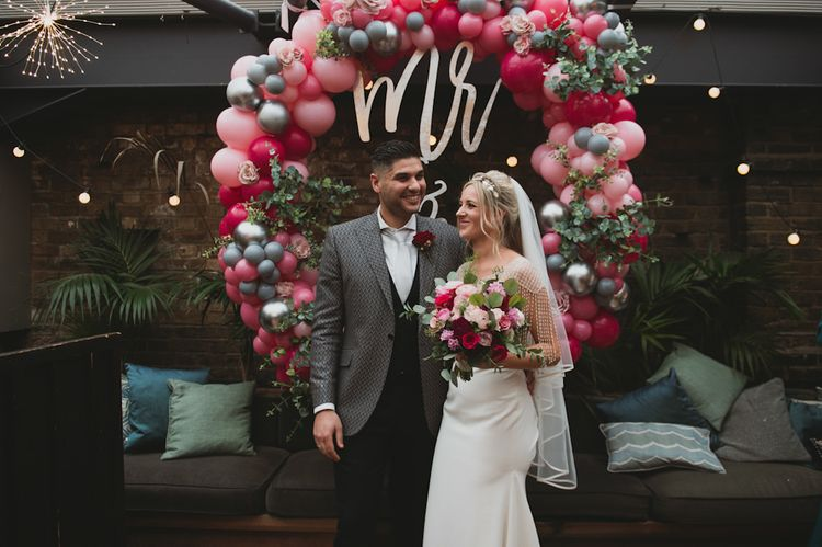 Bride and Groom In Front of Balloon Wedding Arch