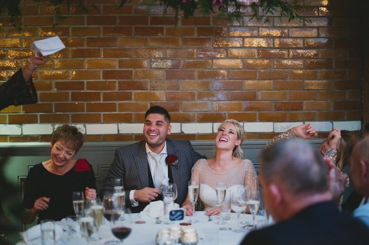 Bride and Groom Enjoy Wedding Speeches During Reception