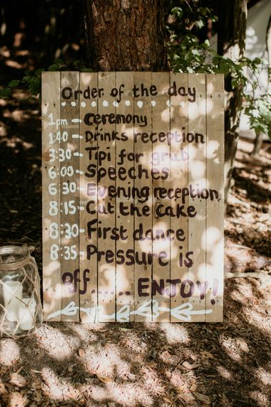 Wooden Order of the Day Wedding Sign | Burgundy Outdoor Woodland Ceremony & Country Tipi & Horse Bar Reception at The Ancient Woodland, Hertfordshire, Planned & Styled by Caroline Hitchcock Events | Alex Wysocki Photography | DgtlCouture Film