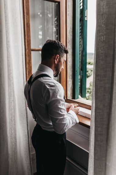 Groom preparations for black and white Italian wedding