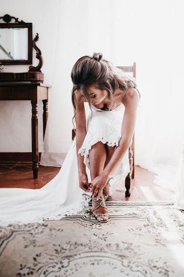 Bride puts on metallic wedding shoes
