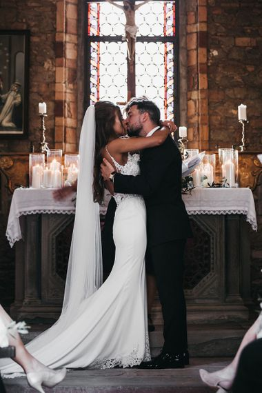 Bride and groom kiss after vows at black and white wedding