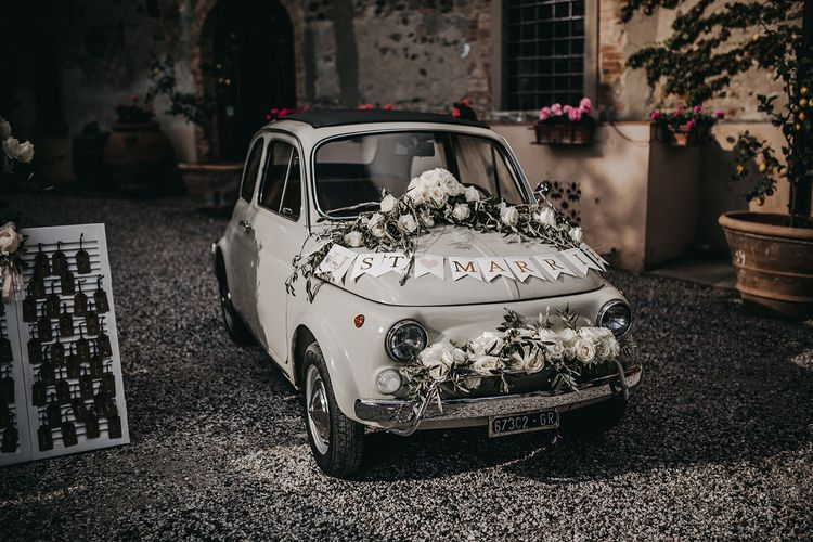 Fiat 500 wedding car decorated with flowers and bunting