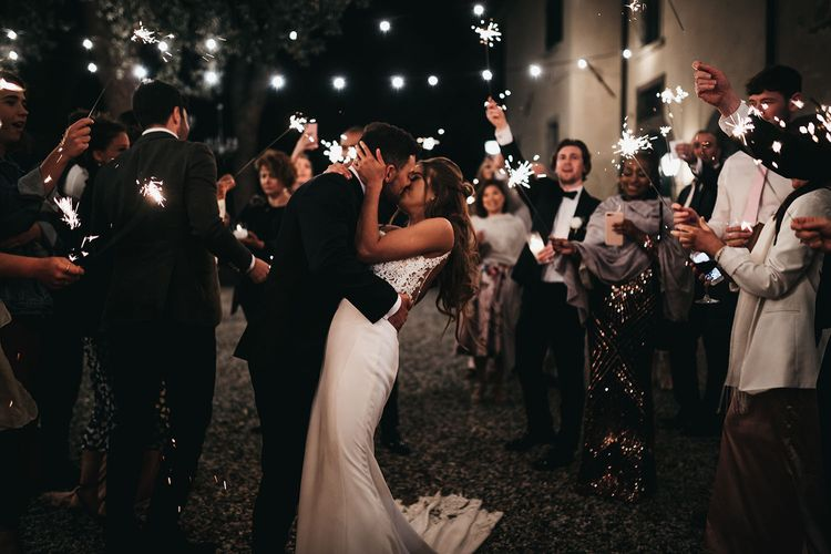 Guests wave sparklers for bride and grooms first dance