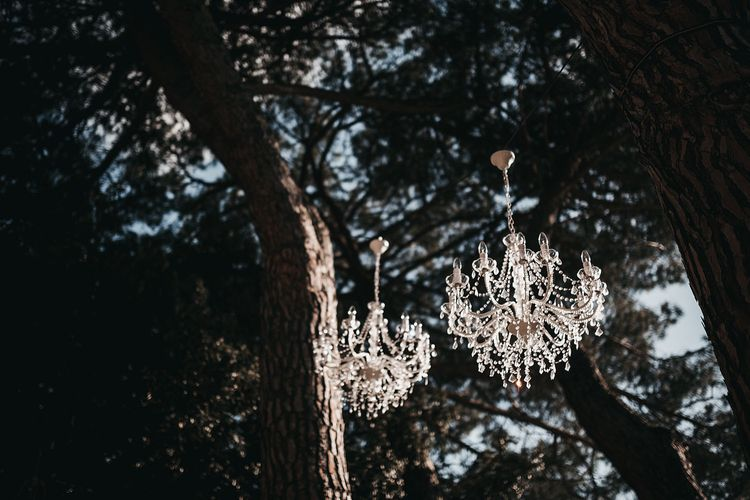 Chandeliers hanging from the tree at black and white wedding in Tuscany