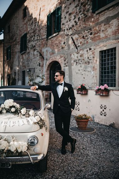 Groom poses in tuxedo next to wedding car at black and white wedding