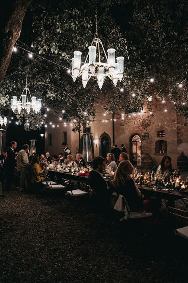 Reception lit up with festoon wedding lighting and chandeliers