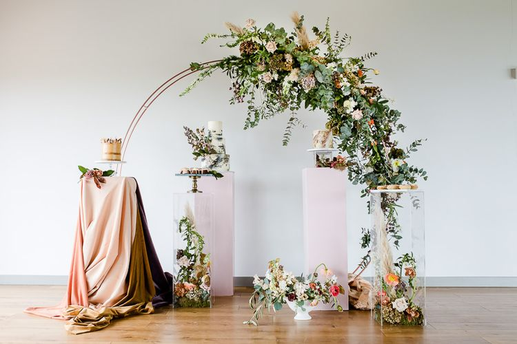 Floral Arch And Perspex Plinth For Wedding Cake Display // Environmentally Conscious Wedding Venue Casterley Barn In Wiltshire Organic Working Farm Stylish Barn Wedding Venue Images Lydia Stamps