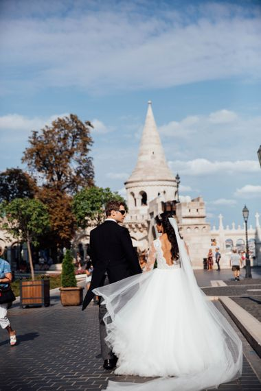 Bride in Pergola Rosa Clara Princess Wedding Dress and Groom in Traditional Morning Suit Walking the Streets on Budapest