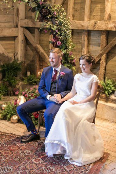 Bride in Jesus Peiro Wedding Dress and Groom in Blue  Hugo Boss Suit Sitting at their Moon Gate Altar