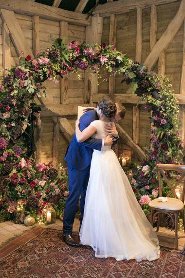 Bride in Jesus Peiro Wedding Dress and Groom in Blue  Hugo Boss Suit Hugging at The Moon Gate Altar