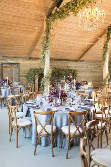 Rustic Barn Wedding Reception with Wooden Chairs and  Floral Centrepieces