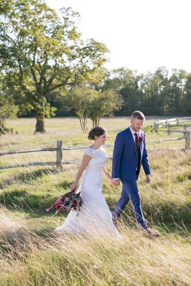 Bride in Jesus Peiro Wedding Dress and Groom in Blue  Hugo Boss Suit Walking Through  the Countryside