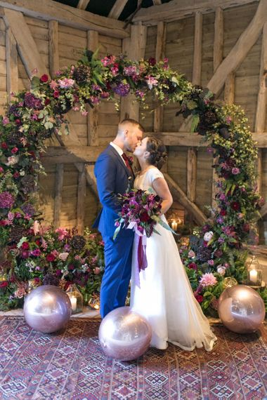 Bride in Jesus Peiro Wedding Dress and Groom in Blue  Hugo Boss Suit Standing in Front of a Floral Moon Gate