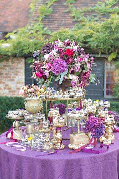 Dessert Table with Purple Table Cloth and Wedding Flowers