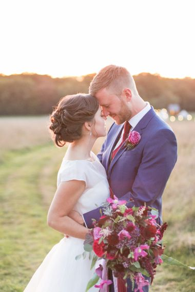 Bride in Jesus Peiro Wedding Dress and Groom in Blue  Hugo Boss Suit Embracing in the Countryside