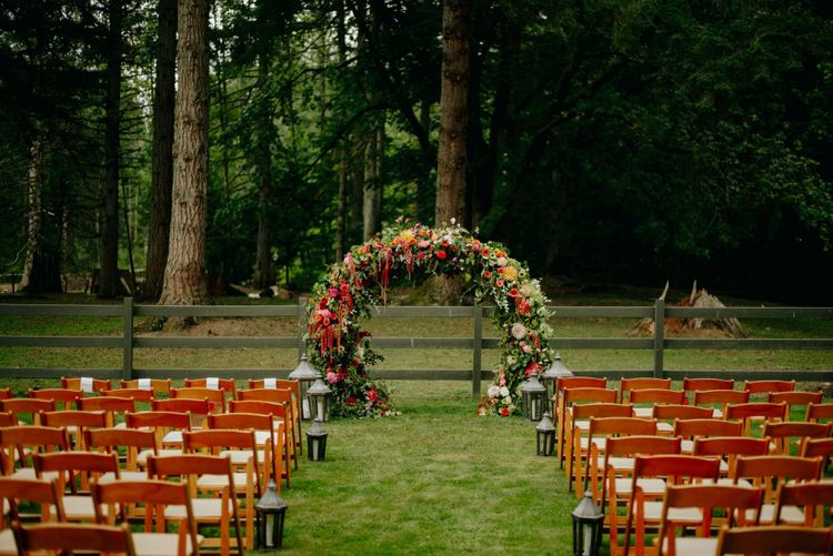 Outdoor wedding ceremony with brightly coloured flower arch