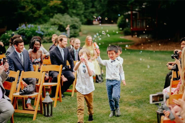 Page boys with bubbles walking down the aisle