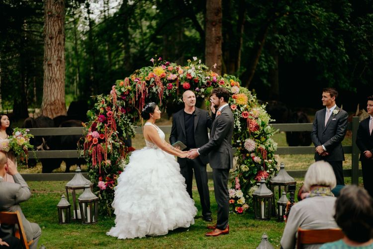 Outdoor civil ceremony in front of a flower arch