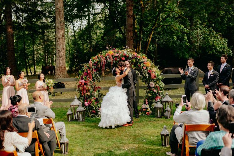Bride and groom kissing in front of the flower arch at outdoor wedding ceremony