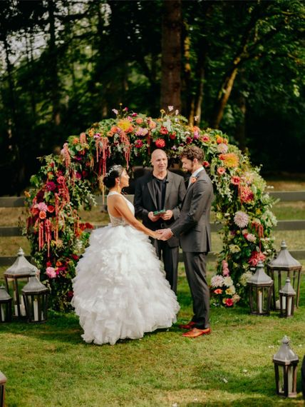 Bride and groom exchanging vows in front of the flower arch