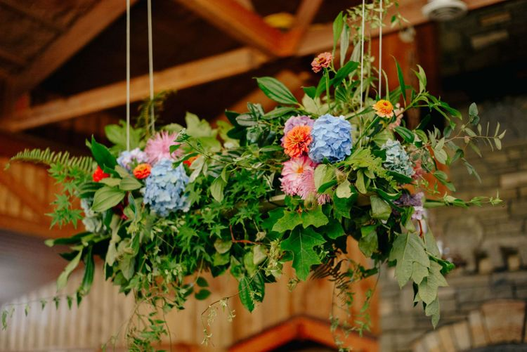 Colourful hanging installation with blue hydrangeas and red dahlias