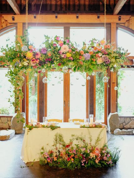 Sweetheart table with brightly coloured flower installation and arrangement