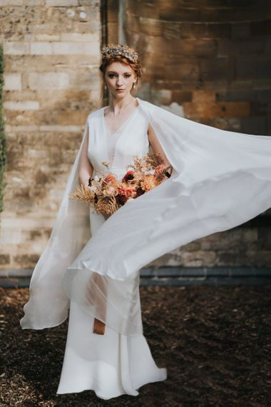 Bride in minimal wedding dress with cape sleeves and orange wedding bouquet