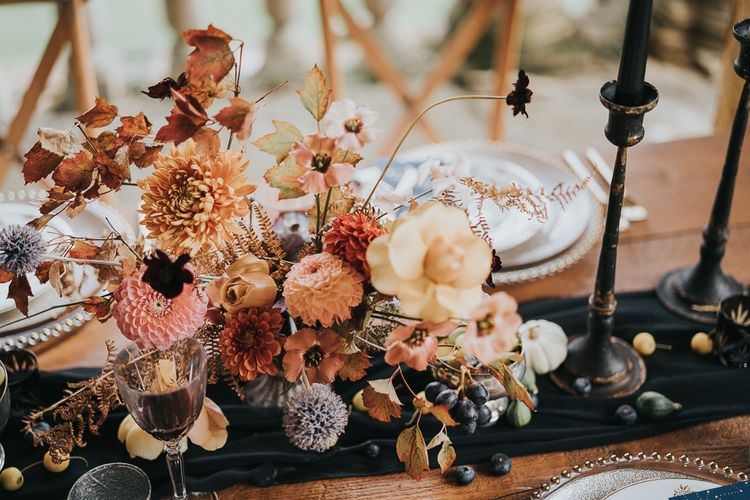 Autumn centrepiece with orange flowers and black candles
