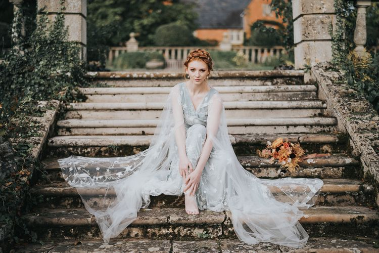 Bride in celestial wedding dress sitting on steps at Stoke Park Pavilions