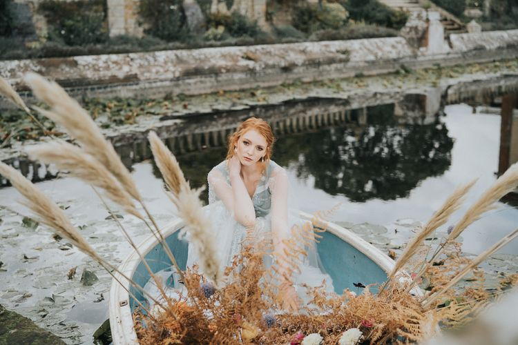 Bride in blue wedding dress sitting in a boat with dried flowers