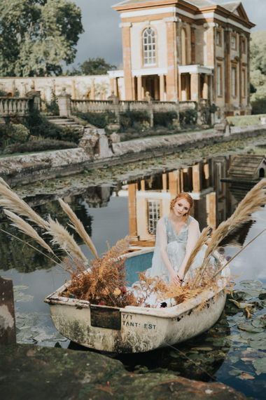 Bride sitting in boat at Stoke Park Pavillions