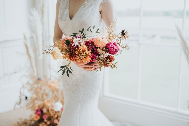 Bride in sparkly wedding dress with pink wedding bouquet