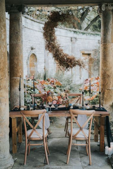 Dried flower moon crescent installation over outdoor tablescape