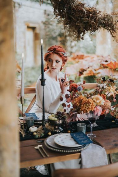 Bride with red hair sitting at autumnal tablescape