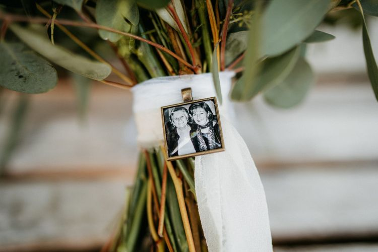 Precious photograph on bouquet ribbon at outdoor wedding