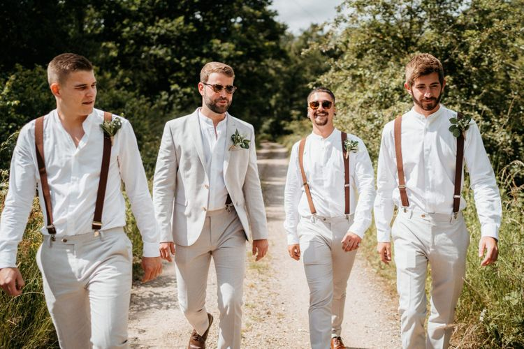 Groom and groomsmen in pale suits and braces