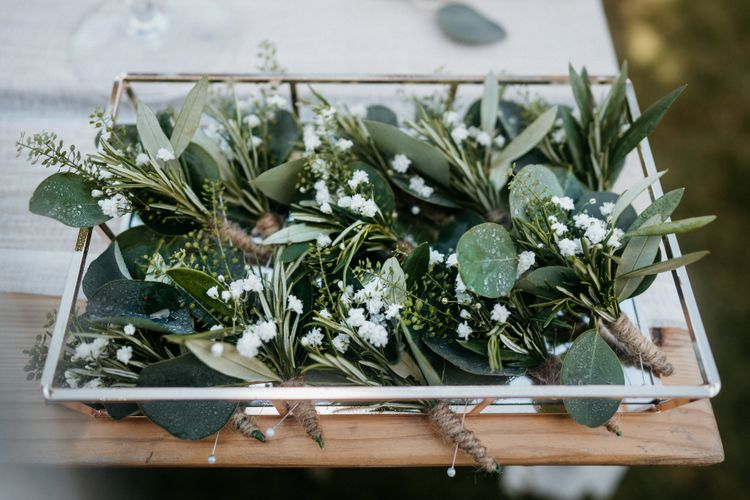 Foliage buttonholes for groom and groomsmen at boho outdoor wedding