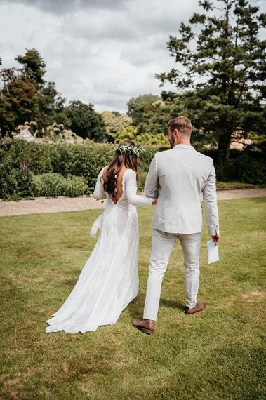 Low back lace wedding dress and pale linen suit for groom