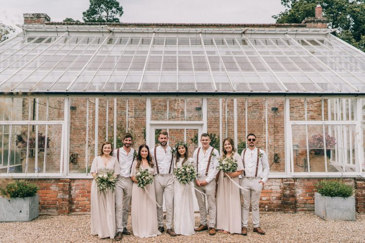 Bridal party and groomsmen in neutral outfits with foliage bouquets