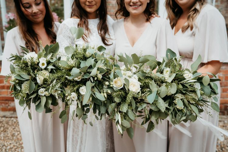 Foliage bouquets for bridesmaids at wedding with donut wall and BBQ meal