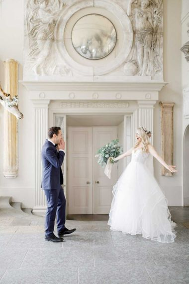 Emotional first look for bride and groom at whimsical wedding