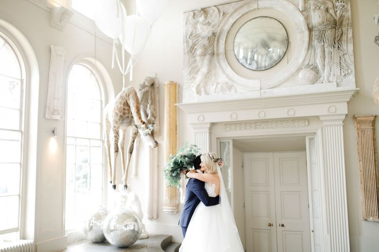 Emotional first look for bride and groom at whimsical wedding beneath quirky wedding  decor